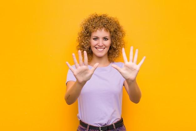 Sorrindo e parecendo amigável, mostrando o número dez ou décimo com a mão para a frente, contando Foto Premium