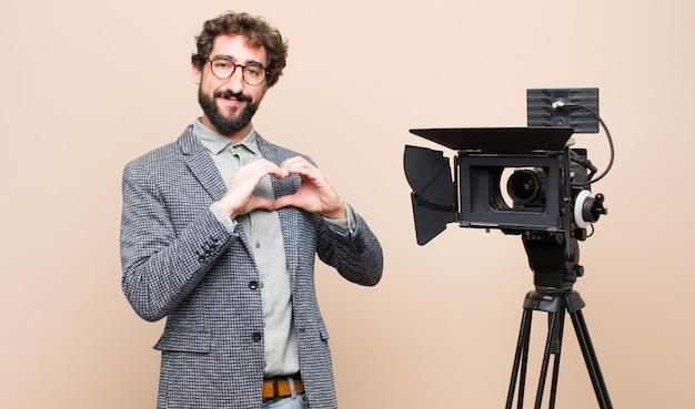 Sorrindo e sentindo-se feliz, fofo, romântico e apaixonado, fazendo formato de coração com as duas mãos Foto Premium