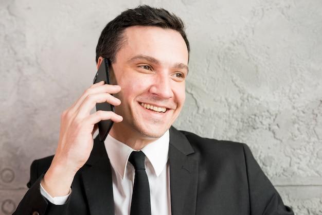 Sorrindo, elegante, homem negócios, falando telefone Foto gratuita