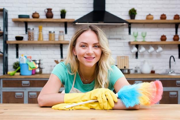 Sorrindo, empregada, inclinar-se, contador cozinha, segurando, espanador pena, olhando câmera Foto gratuita
