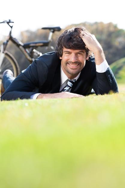 Sorrindo empresário descansando na grama Foto gratuita