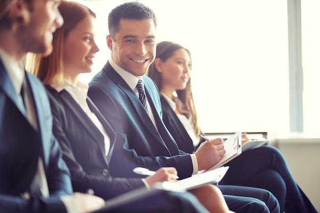 Sorrindo empresário em uma convenção Foto gratuita