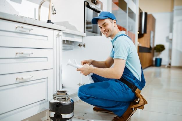 Sorrindo, encanador masculino de uniforme detém o tubo de drenagem na cozinha. handywoman com pia de conserto de bolsa de ferramentas, serviço de equipamento sanitário em casa Foto Premium