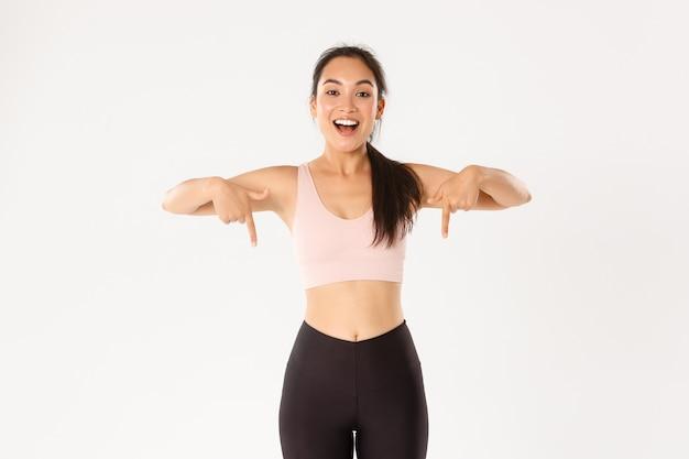Sorrindo energizada menina asiática fitness, atleta feminina, convidando para um evento, mostrando o anúncio de equipamento de treino, apontando o dedo para baixo, seu logotipo. Foto Premium