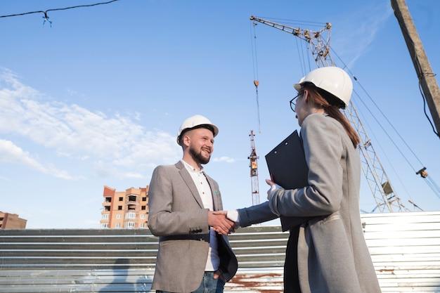Sorrindo engenheiros apertando as mãos no canteiro de obras para projeto arquitetônico Foto gratuita