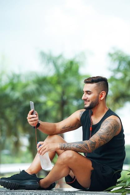 Sorrindo esportista usando telefone ao ar livre Foto gratuita