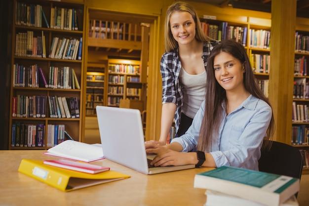 Sorrindo, estudantes, usando computador portátil, em, biblioteca Foto Premium