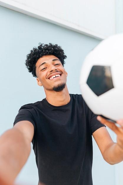 Sorrindo, étnico, homem, com, futebol, olhando câmera Foto gratuita