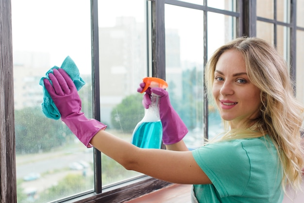 Sorrindo faxineiro limpando a janela de vidro com pano olhando para a câmera Foto gratuita