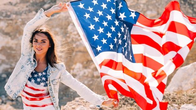 Sorrindo, femininas, com, bandeira, olhando câmera Foto gratuita