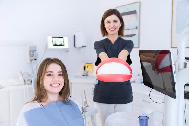 Sorrindo, femininas, paciente, frente, odontólogo, segurando, dentes, modelo, em, clínica Foto gratuita
