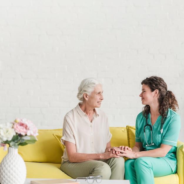 Sorrindo, femininas, sênior, paciente, e, enfermeira, segurando, cada, outro, mão Foto gratuita