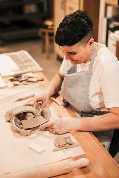 Sorrindo feminino potter dando forma ao molde de barro na mesa de madeira Foto gratuita