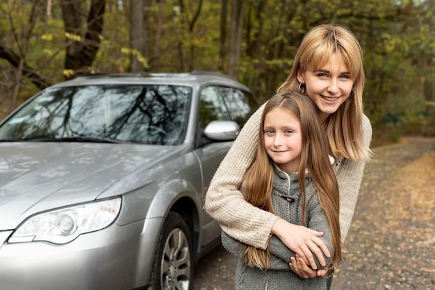 Sorrindo, filha e mãe posando na fonte do carro Foto gratuita
