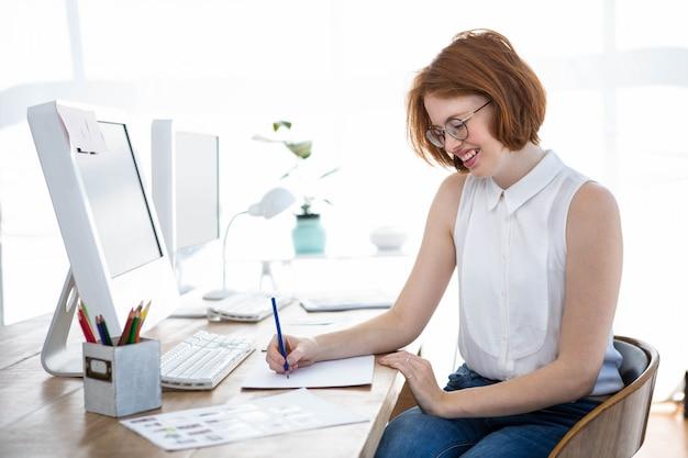 Sorrindo hipster mulher de negócios, desenhando em papel na mesa dela Foto Premium