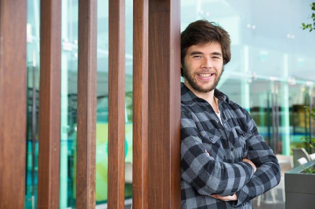 Sorrindo homem atraente em pé ao ar livre com os braços cruzados Foto gratuita