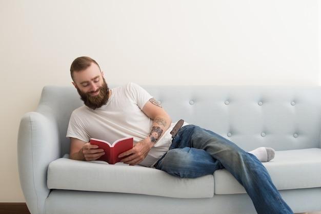 Sorrindo, homem barbudo, mentindo sofá, e, livro leitura Foto gratuita