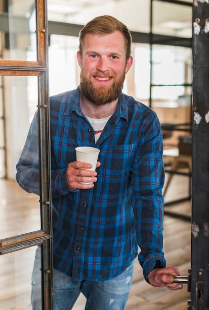 Sorrindo homem barbudo segurando o copo de café descartável ao abrir a porta Foto gratuita