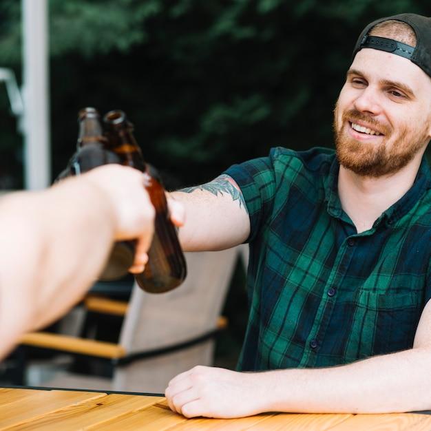 Sorrindo homem brindando garrafas de cerveja com seu amigo Foto gratuita