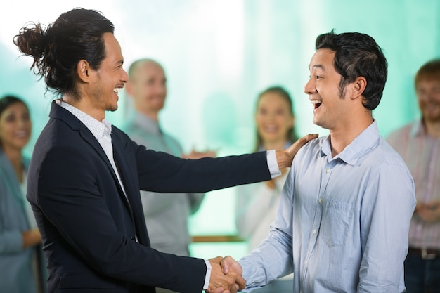 Sorrindo homem de negócio asiático cumprimento masculino parceiro Foto gratuita