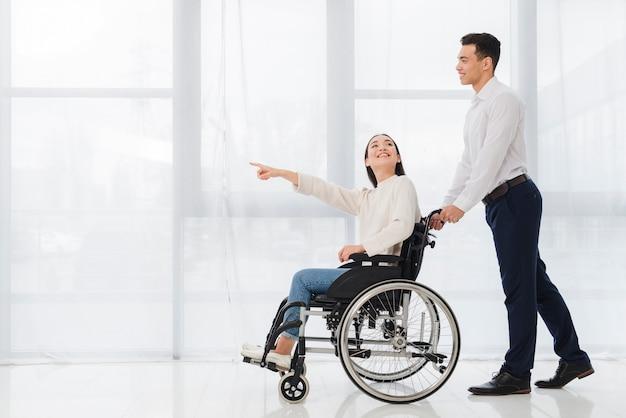 Sorrindo, homem jovem, ajudando, um, mulher jovem, sentando, ligado, cadeira rodas, apontar, dela, dedo, algo Foto gratuita