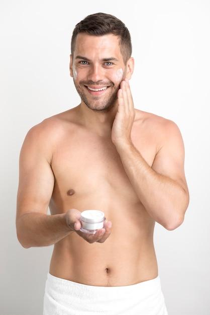 Sorrindo, homem jovem, aplicando, creme rosto, olhando câmera, ficar, contra, fundo branco Foto gratuita