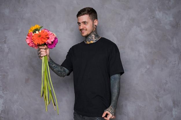 Sorrindo, homem jovem, com, tatuagem, ligado, seu, corporal, oferecendo, a, gerbera, flores, contra, parede cinza Foto gratuita