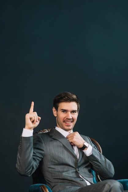 Sorrindo, homem jovem, dedo apontando, cima, contra, experiência preta Foto gratuita