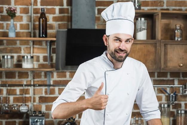 Sorrindo, homem jovem, ficar, em, cozinha, mostrando, polegar cima, sinal Foto gratuita