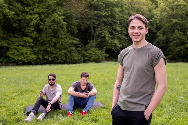 Sorrindo, homem jovem, ficar, ligado, campo, com, amigos Foto gratuita
