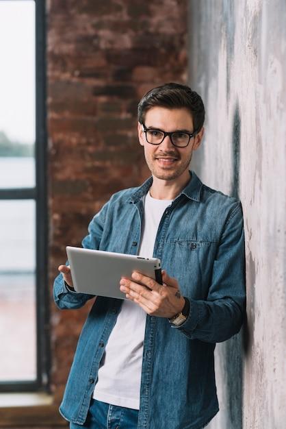Sorrindo, homem jovem, inclinar-se, parede, segurando, tablete digital, em, mãos Foto gratuita