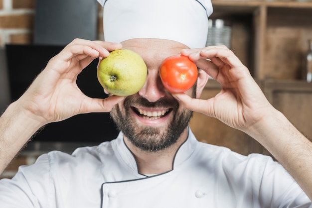 Sorrindo, homem jovem, segurando, fresco, tomate maduro, e, maçã, frente, seu, olhos Foto gratuita