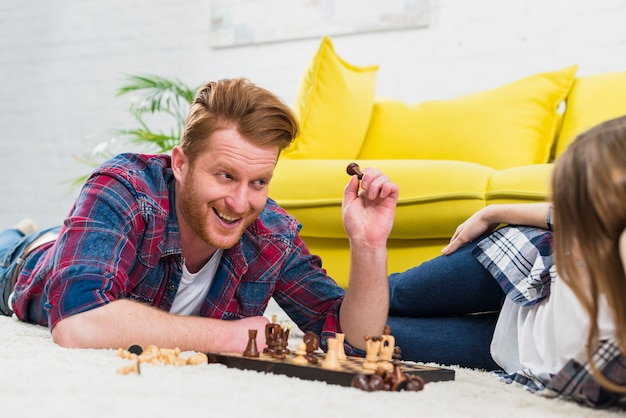 Sorrindo, homem jovem, segurando, pedaço xadrez, olhar, dela, namorada, mentindo, ligado, tapete Foto gratuita
