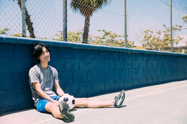 Sorrindo, homem jovem, sentando, em, cerca, com, futebol Foto gratuita