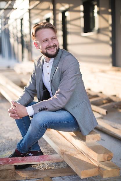 Sorrindo, homem jovem, sentando, ligado, prancha madeira, em, ao ar livre Foto gratuita