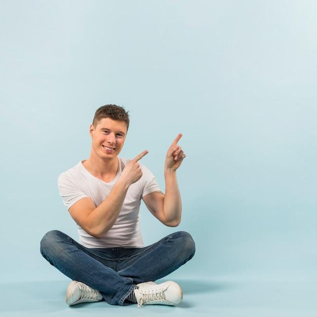Sorrindo, homem jovem, sentar chão, apontar, seu, dedos cima, contra, azul, fundo Foto gratuita