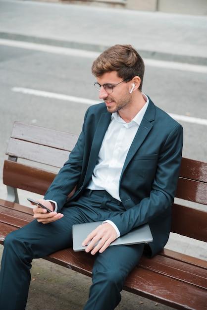 Sorrindo, homem jovem, sentar-se banco, rua, usando, telefone móvel, com, sem fio, fone ouvido Foto gratuita