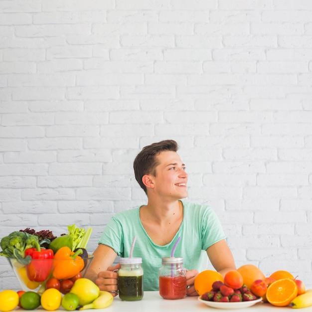 Sorrindo, homem jovem, sentar, tabela, com, maduro, legumes frescos, e, frutas Foto gratuita