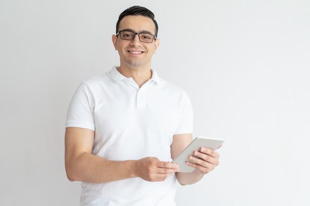 Sorrindo, homem jovem, usando, tabuleta, computador Foto gratuita