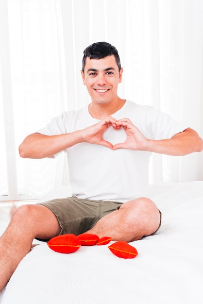 Sorrindo, homem, mostrando, símbolo, de, coração Foto gratuita