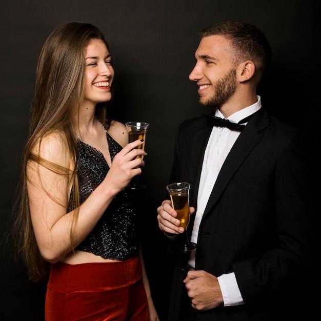 Sorrindo, homem mulher, em, jaqueta jantar, e, noite, desgaste, com, copos bebidas Foto gratuita