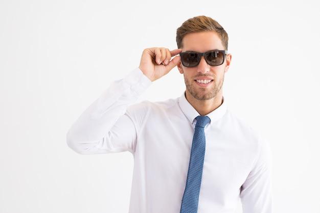 Sorrindo, homem negócio, ajustar, óculos de sol, e, olhando câmera ... 1246a5ab1c