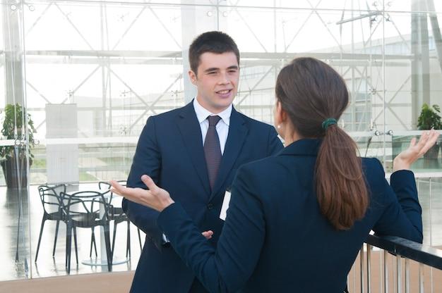 Sorrindo, homem negócio, falando, com, femininas, colega, ao ar livre Foto gratuita