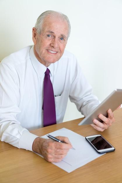 Sorrindo, homem negócio sênior, olhando câmera, escrita, e, usando, tabuleta, computador Foto Premium