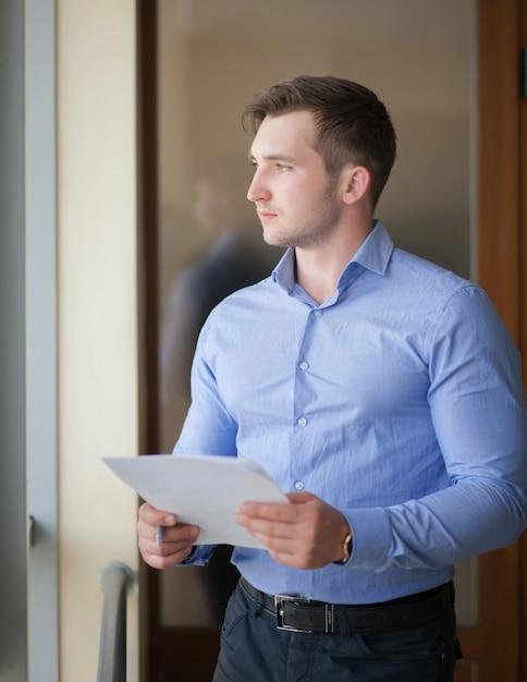 Sorrindo, homem negócios fica, pela janela, em, escritório, e, leitura, papel Foto Premium
