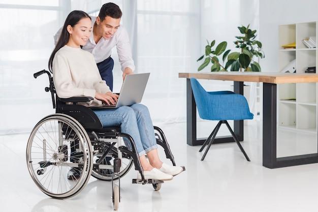 Sorrindo, homem negócios, mostrando, algo, para, seu, incapacitado, mulher jovem, ligado, laptop, em, escritório Foto gratuita