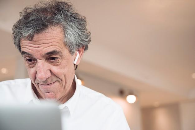 Sorrindo, homem negócios sênior, olhar, laptop Foto gratuita