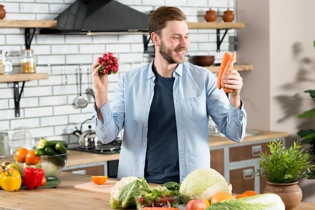 Sorrindo, homem, olhar, laranja, cenoura, ficar, atrás de, contador cozinha Foto gratuita