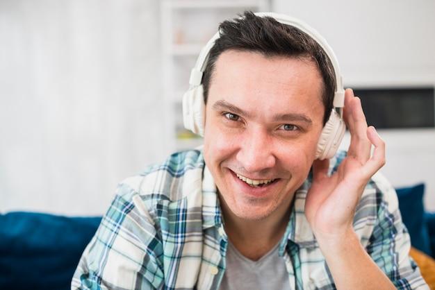 Sorrindo homem ouvindo música em fones de ouvido no sofá Foto gratuita