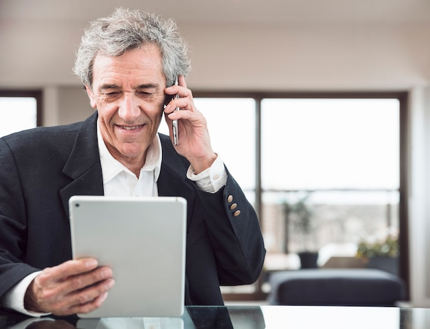 Sorrindo, homem sênior, falando telefone móvel, olhar, tablete digital, em, local trabalho Foto gratuita